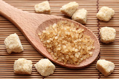 Brown cane sugar crystals in a wooden spoon. On bamboo napkin. Close-up Stock Photos