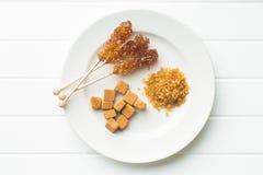 Brown cane sugar, cube sugar and crystalline sugar. Stock Images