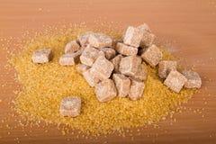 Brown cane sugar cubes and crystal sugar Royalty Free Stock Images