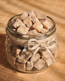 Brown cane sugar cubes in the glass jar Stock Images