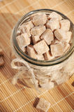 Brown cane sugar cubes in the glass jar Stock Photo
