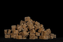 Brown cane sugar. Brown sugar cubes piled on a black background Royalty Free Stock Images
