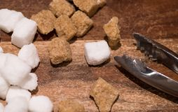 Brown cane and white sugar cubes. Close up. Brown cane and white sugar cubes on wooden background and sugar tongs stock photography