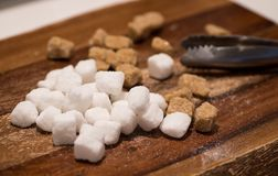 Brown cane and white sugar cubes. On wooden background and sugar tongs stock photos