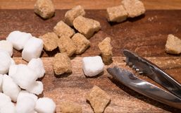 Brown cane and white sugar cubes on wooden table. Close up. Brown cane and white sugar cubes on wooden background and sugar tongs royalty free stock images