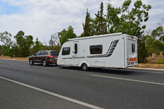 Car Towing A Caravan. A brown car towing a large caravan on an empty road royalty free stock image