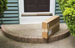 Package left on stoop by front door. A brown cardboard box is left on the front stoop after being delivered while no one was home royalty free stock images