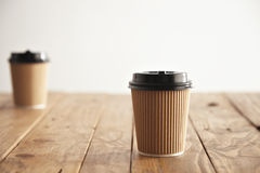 Brown cardboard take away paper cups with black caps set Royalty Free Stock Photos
