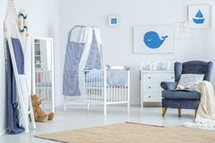 Brown carpet in baby`s room. Brown carpet on the floor in baby`s room with striped veil above crib near mirror, plush toy and armchair stock images