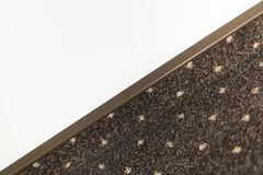Brown carpet floor with a white dots with a carpet baseboard on a white wall. royalty free stock images