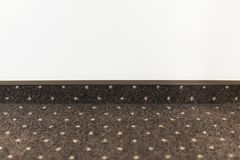 Brown carpet floor with a white dots with a carpet baseboard on a white wall. stock image