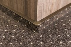 Brown carpet floor with a white dots with a carpet baseboard on a wood-based panels wall. royalty free stock photo