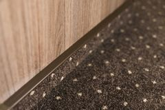 Brown carpet floor with a white dots with a carpet baseboard on a wood-based panels wall. royalty free stock images