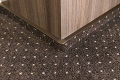 Brown carpet floor with a white dots with a carpet baseboard on a wood-based panels wall. stock images