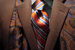 Brown cashmere coat, patterned silk scarf and tie. Close-up of a brown cashmere coat with patterned silk scarf, orange & blue striped tie royalty free stock images