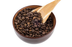 Brown ceramic bowl with coffee beans and bamboo spoon Royalty Free Stock Photos