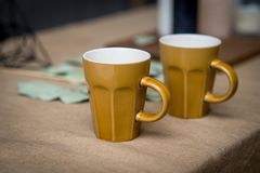 Brown ceramic coffee cups on burlap. selective focus royalty free stock photos