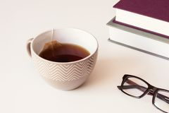 Brown ceramic cup with tea and paper tea bags, Reading Glasses and books on table. Brown ceramic cup with black tea and paper tea bags, Reading Glasses and Royalty Free Stock Image