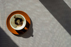 Brown ceramic cup with coffee grounds on saucer Royalty Free Stock Images