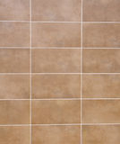 Brown ceramic tiles with white fugue on wall. Closeup Stock Image