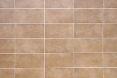 Brown ceramic tiles with white fugue on wall. Closeup Stock Photo
