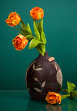 Brown ceramic vase and four flowers on green Royalty Free Stock Photos