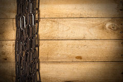 Brown Chain on a Wooden Background Royalty Free Stock Photo