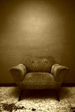 Brown Chair. A well worn chair set against a wall in a room in Mexico Stock Photo