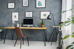 Brown chair at desk in grey freelancer`s interior with lamp and stock image