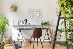 Brown chair at desk in white boho home office interior with plan stock images