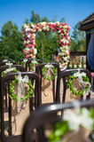 Brown chairs decorated for wedding ceremony. Backs of the brown chairs are decorated with wedding wreath. In the background a beautiful floral arch. Selective Royalty Free Stock Images