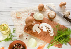 Brown champignon mushrooms on a cutting board. White wooden desk herbs and onions. Stock Photos