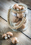 Brown champignon mushrooms on the wooden background. Brown champignon mushrooms in the jar on the wooden background Stock Photography