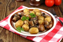Brown champignons with rosemary potato on wood background Stock Photography