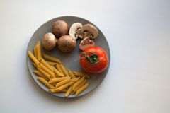 Brown champignons, tomato and penne rigate pasta on plate from above stock photos