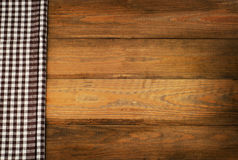 Brown checkered Tablecloth textile on a old wooden background Royalty Free Stock Image