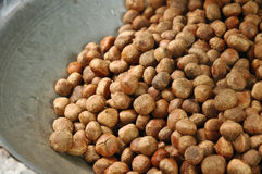 Brown chestnut beans roasting in a silver pan Stock Image