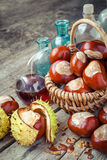Brown chestnuts in basket and vials with tincture on old table Royalty Free Stock Photo