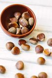 Brown chestnuts over wooden surface. Brown chestnuts in bowl over white wooden surface Royalty Free Stock Photo