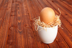 Brown chicken egg arranged in a cup with dried straw Stock Image