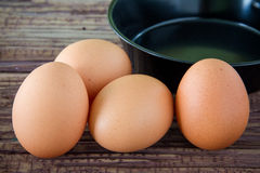 Brown chicken egg and iron pan on the table. Stock Photos