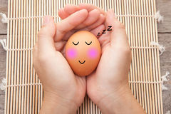 Brown chicken egg sleeping with happy face on woman hand. Royalty Free Stock Images