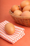 Brown chicken egg on vintage tablecloth and eggs in the basket Royalty Free Stock Photography