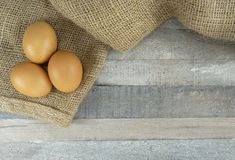 Brown chicken eggs on burlap over wooden background. Brown chicken eggs on burlap/hessian over natural wooden background/ restaurant or easter decoration stock image
