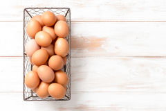 Brown Chicken Eggs in Mesh Wire Tray with Copy Space. Brown chicken eggs in a mesh wire tray over a wooden panel background with copy space royalty free stock images