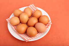 Brown chicken eggs on vintage tablecloth on white plate Stock Images