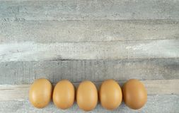 5 Brown chicken eggs at wooden background. 5 Brown chicken eggs at natural wooden background/ decoration for restaurant or spring easter celebration royalty free stock image