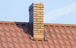 Brown chimney on roof of house on sunny day Royalty Free Stock Photos