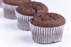 Brown chocolate muffins arranged over white background Royalty Free Stock Photography