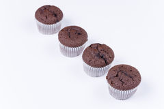 Brown chocolate muffins arranged over white background Stock Images
